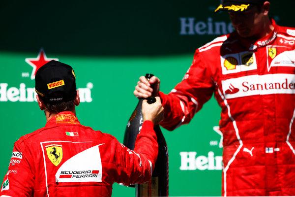 Interlagos, Sao Paulo, Brazil. Sunday 12 November 2017. Winner Sebastian Vettel, Ferrari, 1st Position, and Kimi Raikkonen, Ferrari, 3rd position, with their champagne on the podium. World Copyright: Andy Hone/LAT Images  ref: Digital Image _ONZ6974