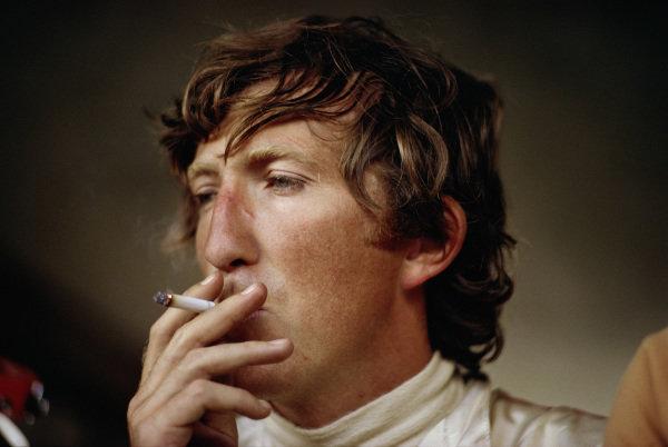 Jochen Rindt smokes a cigarette in the pits.