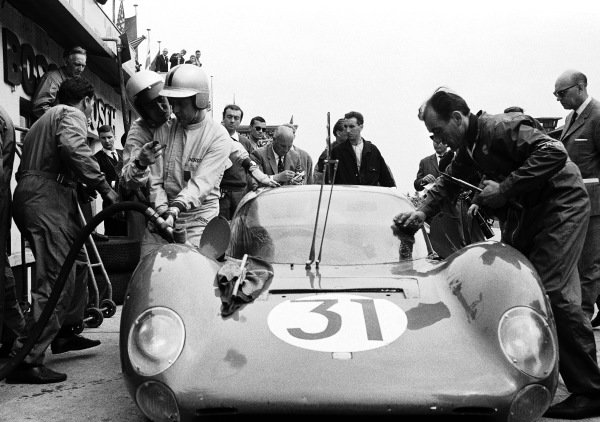 Lorenzo Bandini gives instructions to his teammate Nino Vaccarella as he refuels their SpA Ferrari SEFAC, Ferrari Dino 166 P 0834 in the pitstop.
