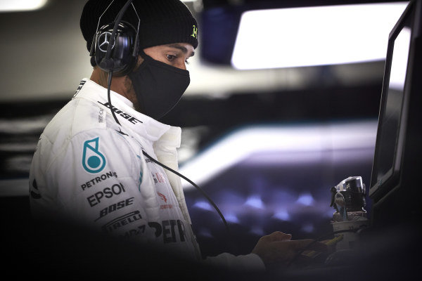 Lewis Hamilton wears a protective face mask in the garage as he prepares to drive a Mercedes W09