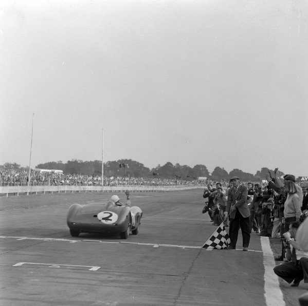 Carroll Shelby / Jack Fairman / Stirling Moss, David Brown, Aston Martin DBR1/300, takes the chequered flag for victory.