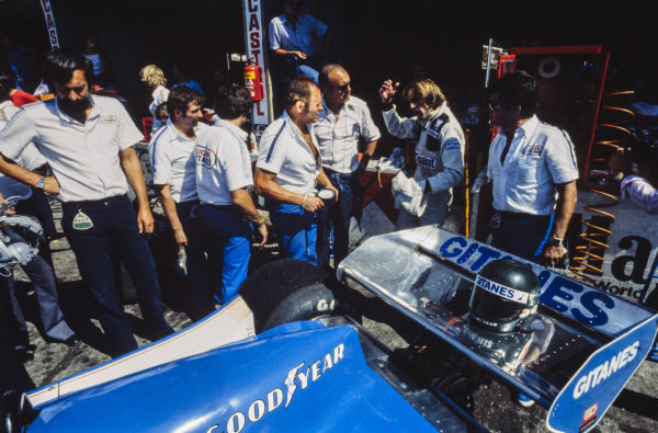 Jacques Laffite talks to Guy Ligier and team members next to his Ligier JS9 Matra.