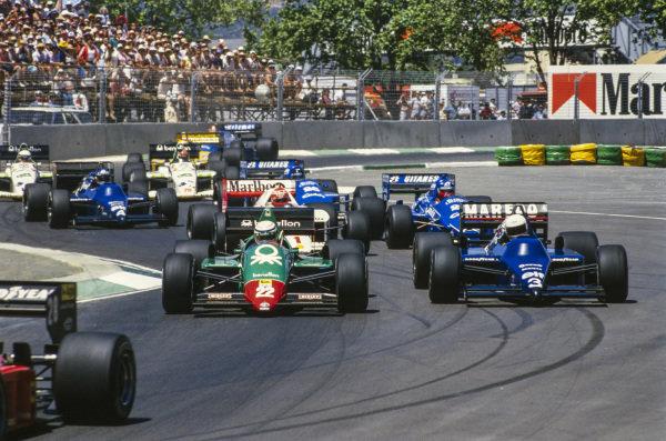 Riccardo Patrese, Alfa Romeo 184T, leads Martin Brundle, Tyrrell 014 Renault, Niki Lauda, McLaren MP4-2B TAG, Philippe Streiff, Ligier JS25 Renault, Jacques Laffite, Ligier JS25 Renault, and Ivan Capelli, Tyrrell 014 Renault, at the start.