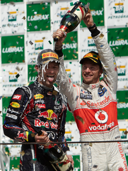 Interlagos, Sao Paulo, Brazil. 27th November 2011. Jenson Button, McLaren MP4-26 Mercedes, 3rd position, delivers a soaking to Mark Webber, Red Bull Racing RB7 Renault, 1st position. Portrait. Podium.  World Copyright: Steve Etherington/LAT Photographic ref: Digital Image SNE28385