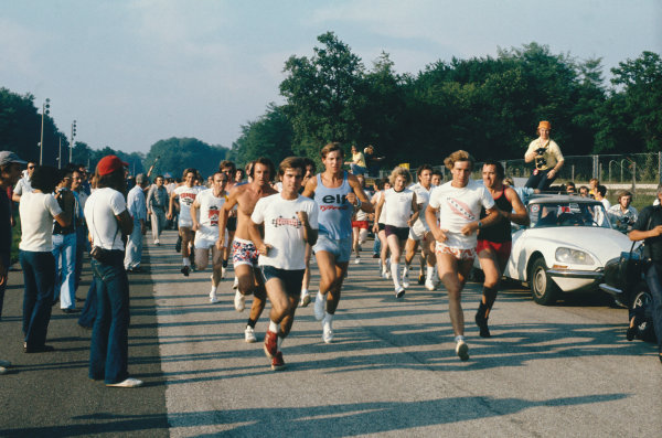 Monza, Italy. 9th September 1973.James Hunt leads the way as a group of drivers, team owners and mechanics run around the circuit for charity. Frank Williams can be seen just to the left, portrait. World Copyright: LAT Photographic.Ref:  73ITA13.