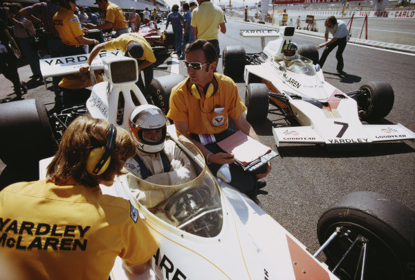 Engineer Phil Kerr sits between Jody Scheckter, McLaren M23 Ford, and Denny Hulme, McLaren M23 Ford.