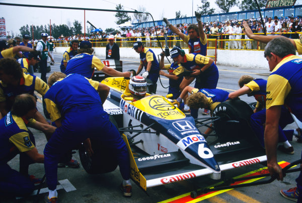 1986 Mexican Grand Prix  Mexico City, Mexico. 9-12th October 1986.  Mechanics perform a tyre change for Nelson Piquet, Williams FW11 Honda, during a pitstop.  Ref: 86MEX35. World copyright: LAT Photographic