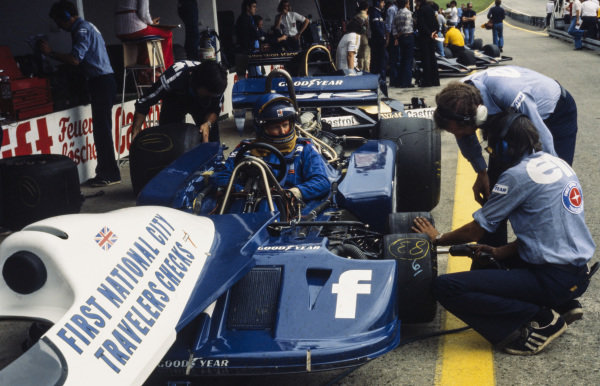 Mechanics put new tyres on Ronnie Peterson's Tyrrell P34 Ford while he waits in the cockpit.