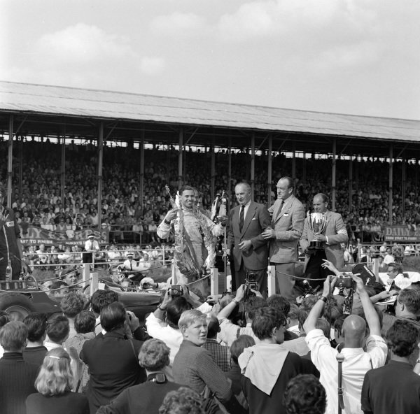 Jim Clark, 1st position, celebrates victory as his winner's trophy is awarded to him.