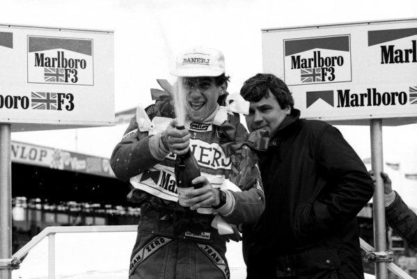 Race winner Ayrton Senna (BRA) West Surrey Racing celebrates on the podium with Williams F1 driver Alan Jones (AUS). British Formula Three Championship, Silverstone, England, 20 March 1983.
