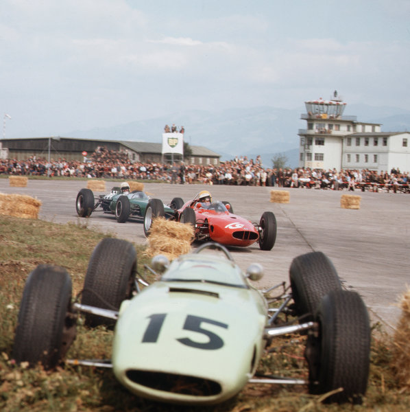 Zeltweg, Austria.21-23 August 1964.Tony Maggs (BRM P57) and Bob Anderson (Brabham BT11-Climax) pass the crashed BRP 1 BRM of Trevor Taylor. They finished in 4th and 3rd positions respectively.Ref-3/1388.World Copyright - LAT Photographic