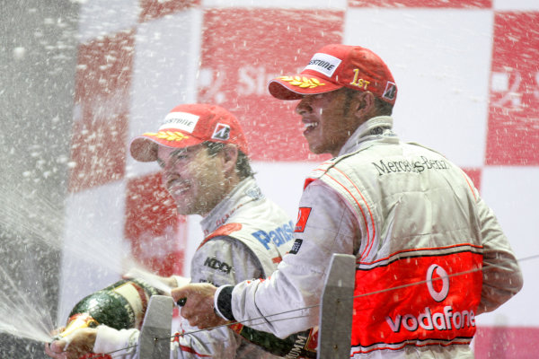 Marina Bay Circuit, Singapore. 27th September 2009. Lewis Hamilton, McLaren MP4-24 Mercedes, 1st position, and Timo Glock, Toyota TF109, 2nd position, spray the champagne. Portrait. Podium.  World Copyright: Glenn Dunbar/LAT Photographic  ref: Digital Image _3GD6870