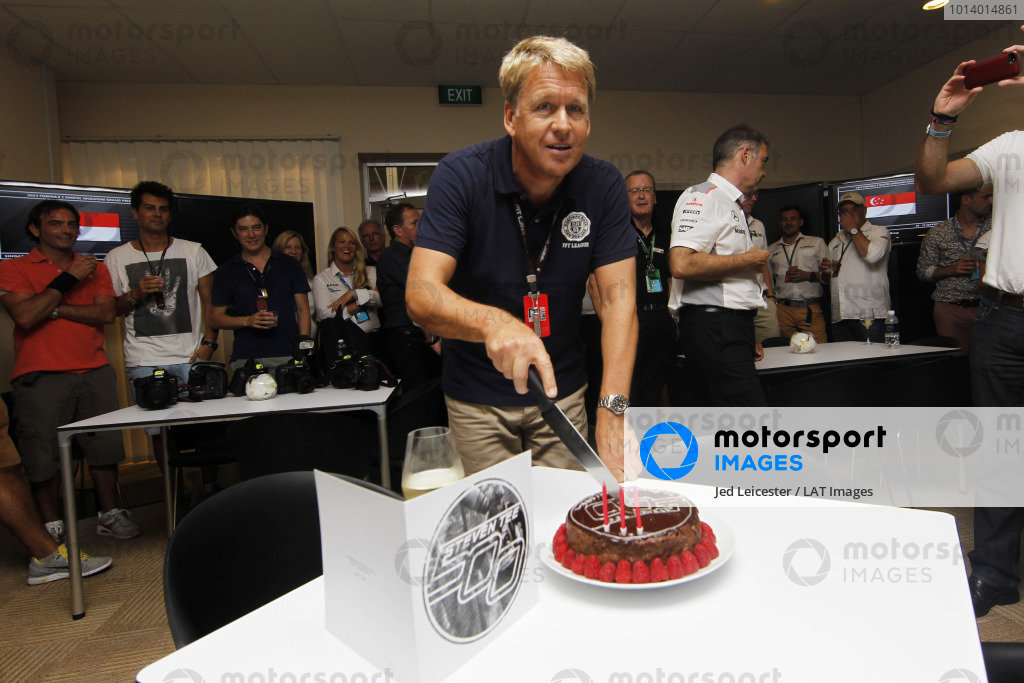 Marina Bay Circuit, Singapore. Saturday 21st September 2013. LAT Chief Photographer Steven Tee cuts a cake at the McLaren hospitality area during a surprise celebration of his 500th Grand Prix. World Copyright: Jed Leicester/LAT Photographic. ref: Digital Image _JED2670