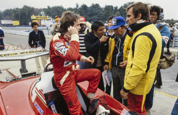 Gilles Villeneuve talks with teammate Carlos Reutemann in the pit lane.