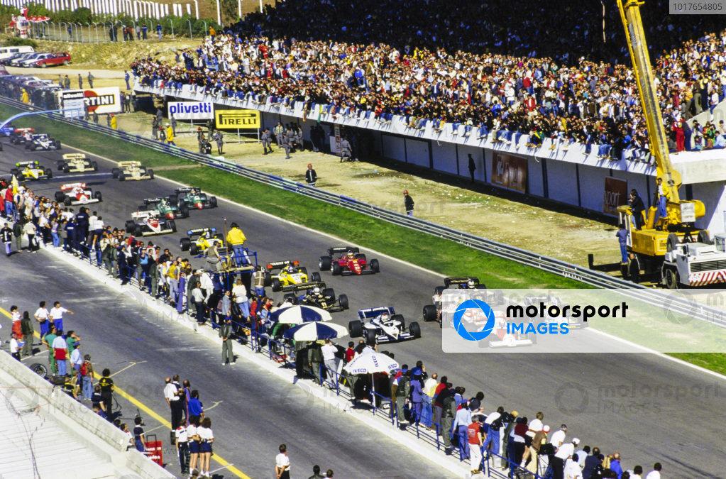 Alain Prost, McLaren MP4-2 TAG, leads the field off the line, ahead of Keke Rosberg, Williams FW09B Honda, Nelson Piquet, Brabham BT53 BMW, Ayrton Senna, Toleman TG184 Hart, and Nigel Mansell, Lotus 95T Renault. Further back is championship contender Niki Lauda, McLaren MP4-2 TAG.