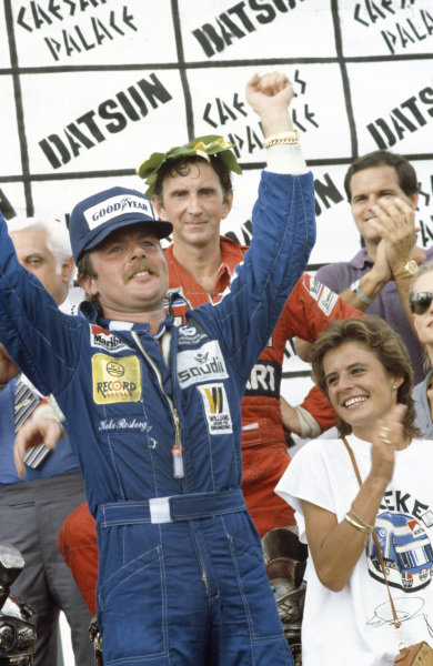 Keke Rosberg and his wife celebrates his world championship win on the podium, while fellow title contender John Watson, 2nd position, is in the background.