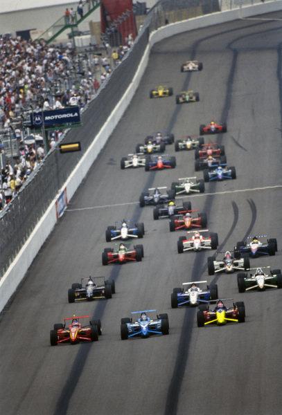 The start of the race, with Jimmy Vasser, Chip Ganassi Racing, Reynard 98i Honda, Greg Moore, Forsythe Racing, Reynard 98i Mercedes, and Tony Kanaan, Tasman Motorsports Group, Reynard 98i Honda, on the front row.