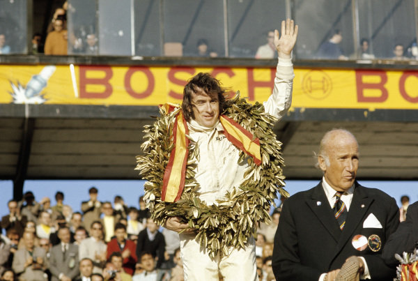 Jackie Stewart celebrates victory on the podium.