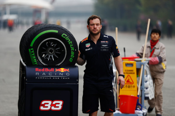 Shanghai International Circuit, Shanghai, China.  Thursday 06 April 2017. A Red Bull team member pushes a trolley of Pirelli tyres in front of a Chinese worker. World Copyright: Glenn Dunbar/LAT Images ref: Digital Image _X4I4798