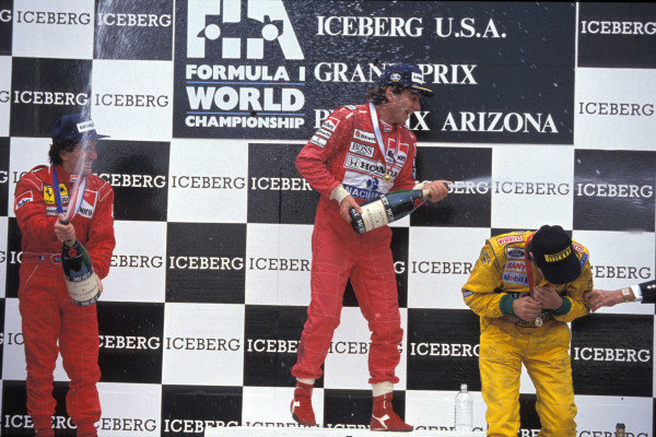 Alain Prost, 2nd position, Ayrton Senna, 1st position, and Nelson Piquet, 3rd position, spray champagne on the podium.