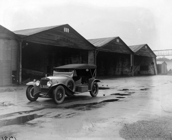 Itala next to aircraft hangars at Brooklands.