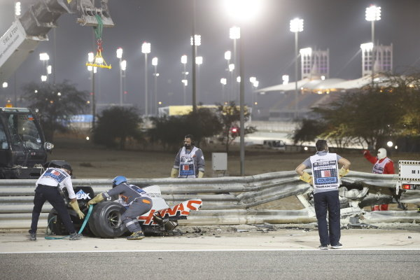 Marshals deal with the wrecked car of Romain Grosjean, Haas VF-20, after a big crash on the opening lap