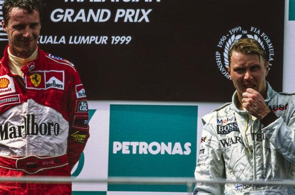 Eddie Irvine, 1st position, and Mika Häkkinen, 3rd position, on the podium.
