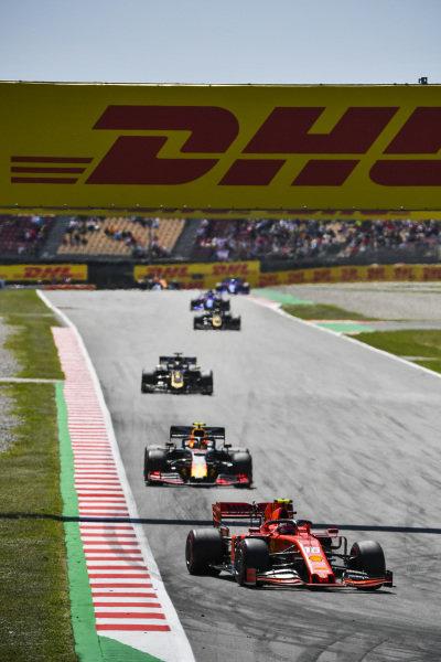 Charles Leclerc, Ferrari SF90, leads Pierre Gasly, Red Bull Racing RB15, and Romain Grosjean, Haas VF-19