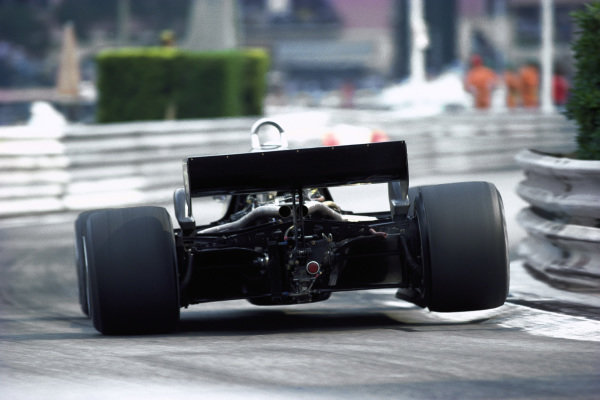 A Lotus 91 Ford, bounces over a kerb at the swimming pool chicane.