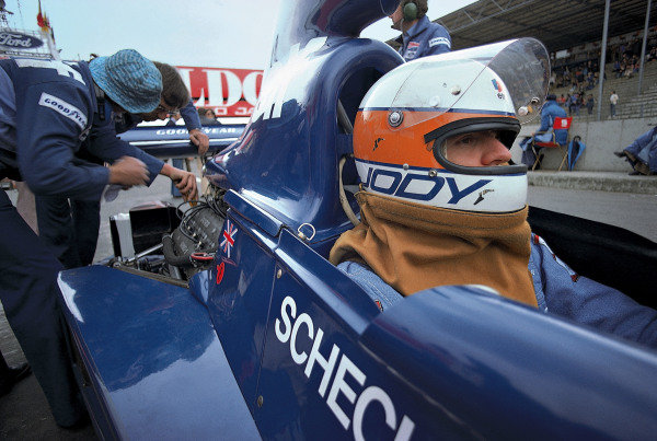 Jody Scheckter waits in the pits as mechanics make the final adjustments to his Tyrrell 007 Ford.