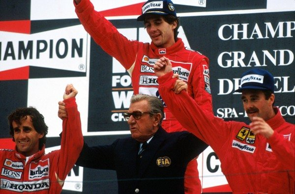 The podium (L to R): Alain Prost (FRA) second; Ayrton Senna (BRA) winner; Nigel Mansell (GBR) third. In the centre is FISA President Jean Marie Balestre letting everyone know who believed the stars of the race to be after their exciting battle. 