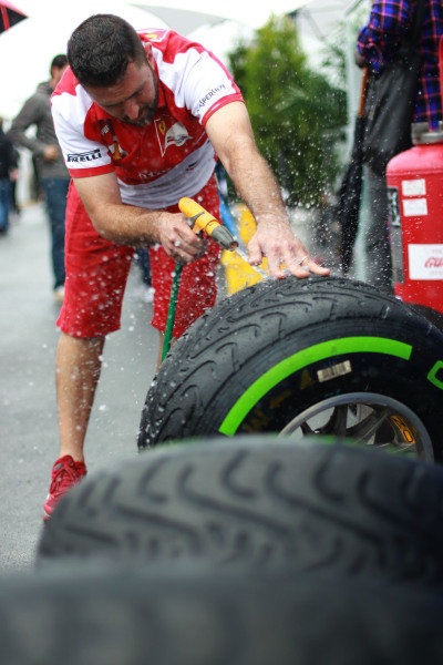 8th June 2013 A Ferrari mechanic washes some tyres World Copyright: Andy Hone/  ref: Digital Image HONY9467