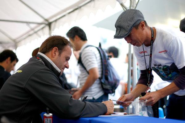 Suzuka Circuit, Suzuka, Japan.1st October 2009.Rubens Barrichello, Brawn GP BGP001 Mercedes signs an autograph for a young fan. Portrait.World Copyright: Charles Coates/LAT Photographicref: Digital Image _26Y8601