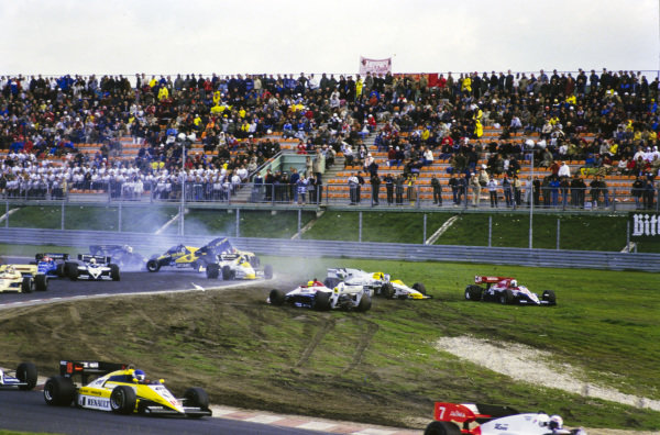 Andrea de Cesaris, Ligier JS23B Renault, cuts across the grass to avoid the carnage caused by Ayrton Senna, Toleman TG184 Hart, colliding with Keke Rosberg, Williams FW09B Honda. Further back, Gerhard Berger, ATS D7 BMW, gets airborne after crashing with Jacques Laffite, Williams FW09B Honda, and Marc Surer, Arrows A7 BMW, prompting Nigel Mansell, Lotus 95T Renault, to take avoiding action. Also in shot is Teo Fabi, Brabham BT53 BMW, colliding with Piercarlo Ghinzani, Osella FA1F Alfa Romeo.