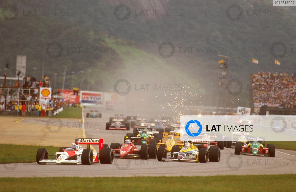 Jacarepagua, Rio de Janeiro, Brazil. 1-3 April 1988. Alain Prost (McLaren MP4/4 Honda) followed by Nigel Mansell (Williams FW12 Judd) and Gerhard Berger (Ferrari F187/88C) at the start.  Ref-88 BRA 08. World Copyright - LAT Photographic