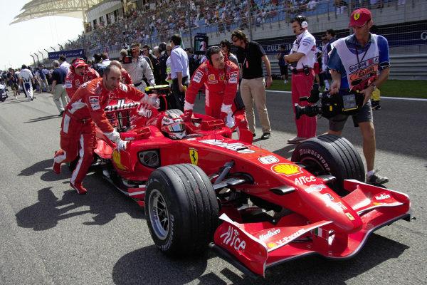 Mechanics push Kimi Räikkönen in his Ferrari F2007 to his grid spot.