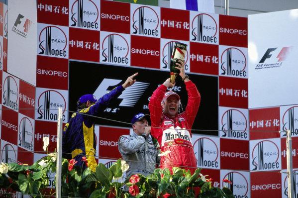 Rubens Barrichello celebrates victory on the podium with Jenson Button, 2nd position, and Kimi Räikkönen, 3rd position.