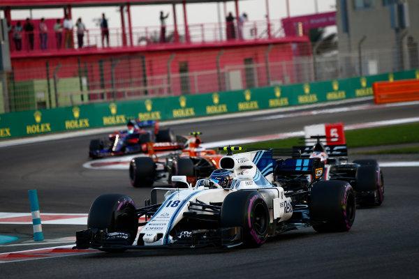 Yas Marina Circuit, Abu Dhabi, United Arab Emirates. Sunday 26 November 2017. Lance Stroll, Williams FW40 Mercedes, leads Romain Grosjean, Haas VF-17, and Stoffel Vandoorne, McLaren MCL32 Honda. World Copyright:Andy Hone/LAT Images  ref: Digital Image _ONY3679