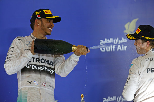 Bahrain International Circuit, Sakhir, Bahrain. Sunday 19 April 2015. Lewis Hamilton, Mercedes AMG, 1st Position, sprays the victory Rose Water at Nico Rosberg, Mercedes AMG, 3rd Position. World Copyright: Alastair Staley/LAT Photographic. ref: Digital Image _79P9050