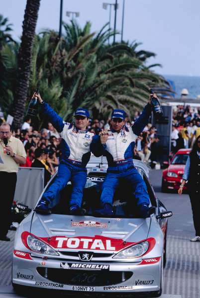 2002 World Rally Championship Sanremo Rally, Italy.  19-22 September 2002. Gilles Panizzi and Herve Panizzi (Peugeot 206 WRC) celebrate their 1st position on the podium. Ref-02 WRC 16. World Copyright - McKlein/LAT Photographic