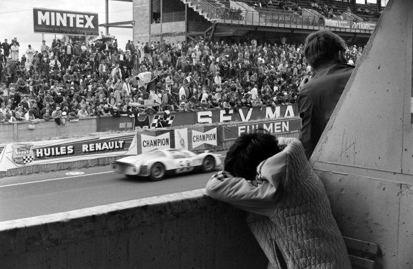 A fan rests above the pits as Günther Klass / Rolf Stommelen, Porsche System Engineering, Porsche 906/6 Carrera 6, passes.