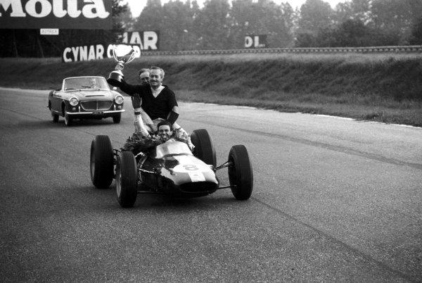 Race winner Jim Clark (GBR) Lotus 25 gives Colin Chapman (GBR) Lotus Team Owner a lift round the circuit complete with the winners trophy. Mike Spence (GBR) Lotus, who retired from the race with a blown engine, joins the pair onboard. Italian Grand Prix, Monza, 8 September 1963.