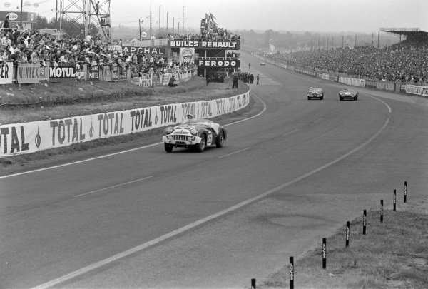 Peter Jopp / Richard Stoop, GBStandard Triumph,Triumph TR 3S, leads as Maurice Trintignant / Paul Frère, David Brown Racing, Aston Martin DBR1/300, battles with Peter Bolton / Michael Rotschild, Standard Triumph, Triumph TR 3S, behind.