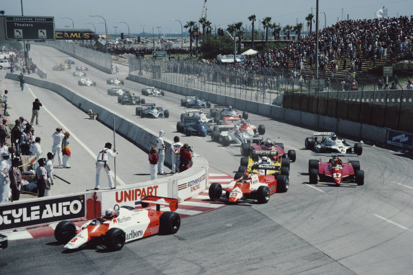Niki Lauda, McLaren MP4-1B Ford, leads Bruno Giacomelli, Alfa Romeo 182, Alain Prost, Renault RE30B, Gilles Villeneuve, Ferrari 126C2, Didier Pironi, Ferrari 126C2, Keke Rosberg, Williams FW07C Ford, and the rest of the pack..
