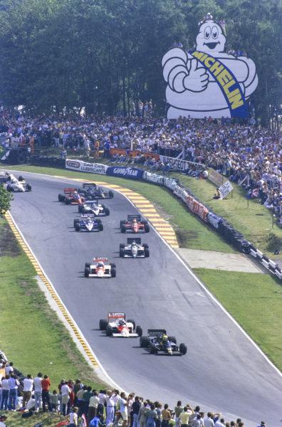 Ayrton Senna, Lotus 98T Renault, leads Keke Rosberg, McLaren MP4-2C TAG, Alain Prost, McLaren MP4-2C TAG, Teo Fabi, Benetton B186 BMW, Michele Alboreto, Ferrari F1/86, René Arnoux, Ligier JS27 Renault, Derek Warwick, Brabham BT55 BMW, Alan Jones, Lola THL-2 Ford, and Johnny Dumfries, Lotus 98T Renault.