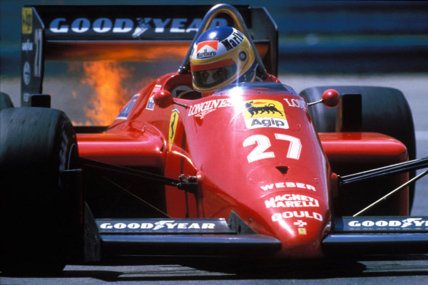 Michele Alboreto, Ferrari 156/85, with flames rising from his engine as he eyes up the next corner.