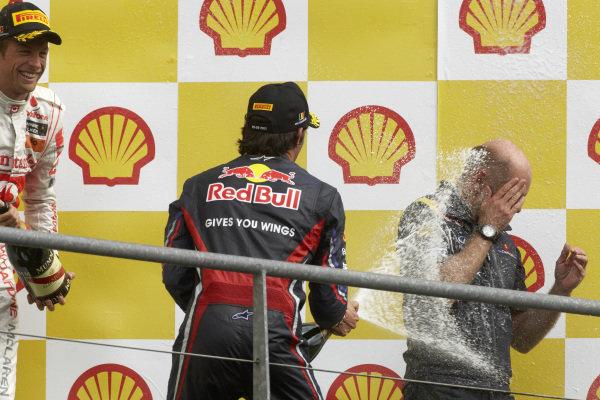 Mark Webber, 2nd position, sprays Adrian Newey on the podium alongside Jenson Button, 3rd position.