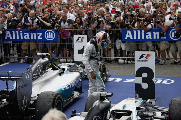 Lewis Hamilton observes damage to his Mercedes F1 W05 Hybrid in parc ferme after the race.