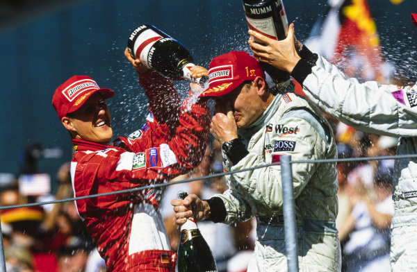 Mika Häkkinen, 1st position, celebrates what would turn out to be his final F1 victory on the podium with Michael Schumacher, 2nd position, and David Coulthard, 3rd position.