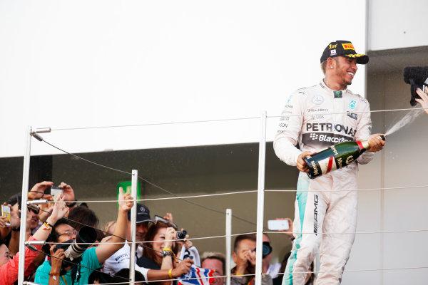 Suzuka Circuit, Suzuka, Japan. Sunday 27 September 2015. Lewis Hamilton, Mercedes AMG, 1st Position, sprays Champagne on the podium. World Copyright: Alastair Staley/LAT Photographic. ref: Digital Image _R6T2552